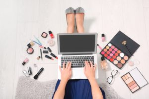 beauty blogger working laptop surrounded my makeup